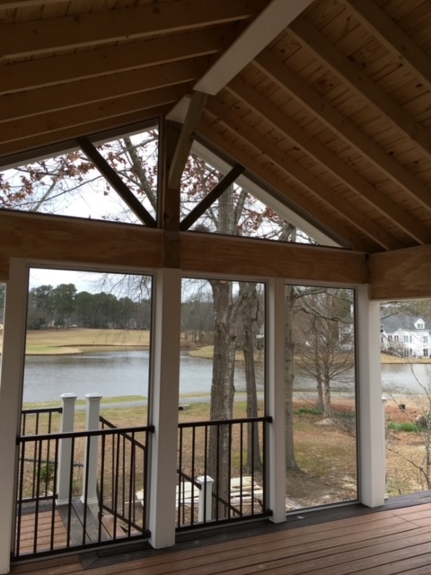 Screened porch on back of home overlooking a small lake.