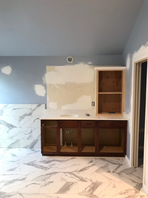 modern bathroom being constructed with marble floor and wall tile.