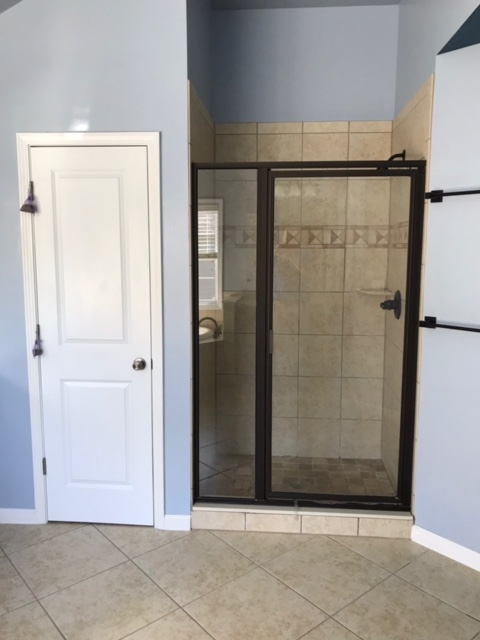 dated bathroom shower with glass door and dated tile.