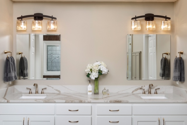 modern bathrooom with white cabinets and stone countertops