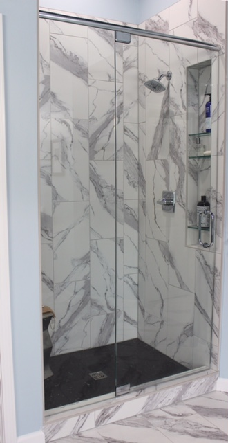 modern shower with glass door and marble tile on walls.