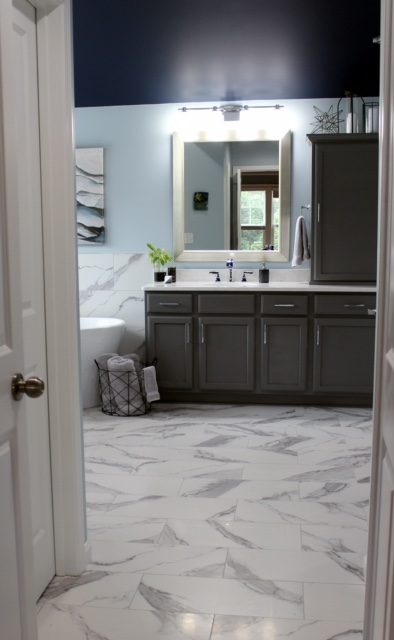 modern bathroom with gray cabinets, marble tile floor and quartz counter. partial view of freestanding tub