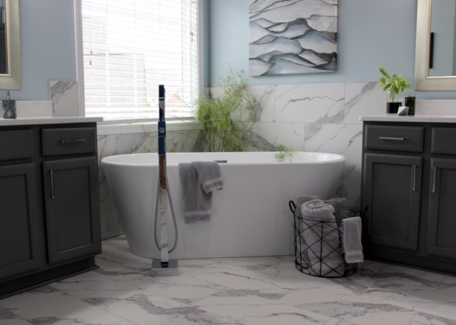 modern bathroom with gray cabinets, marble tile floor and quartz counter. freestanding tub between cabinets