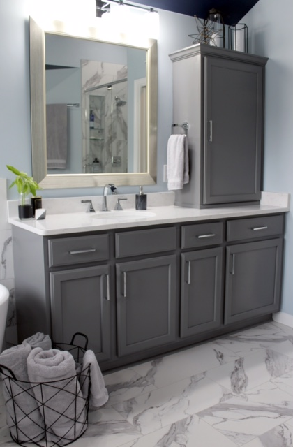 modern bathroom with gray cabinets, marble tile floor and quartz counter