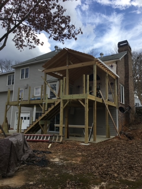 back of large home with wooden deck and screened porch being constructed.