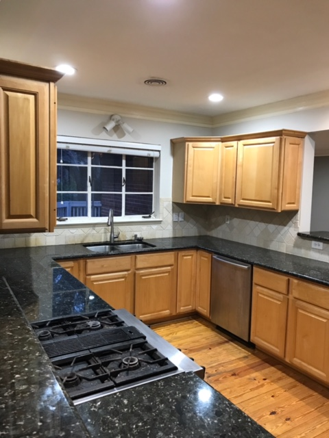 dated kitchen with 2-tier countertops and dark granite counters