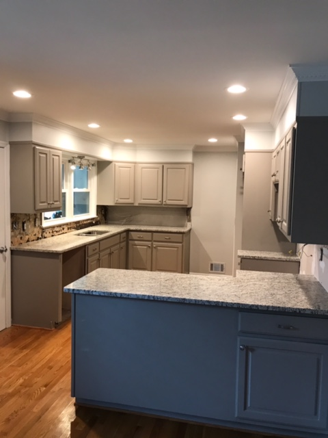 modern kitchen with gray cabinets and black appliances
