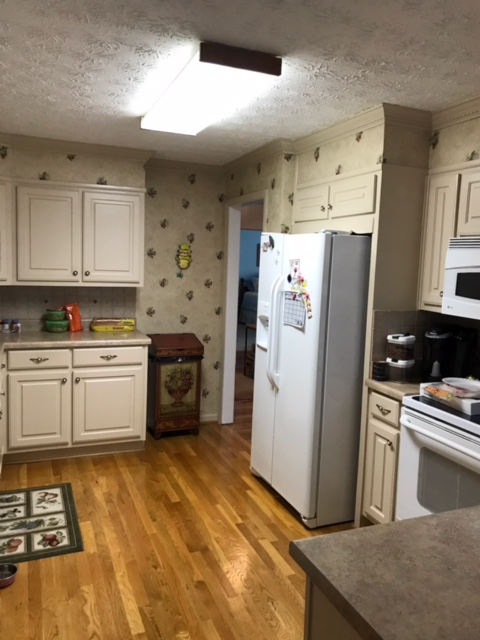 dated kitchen with wallpaper and dated appliances
