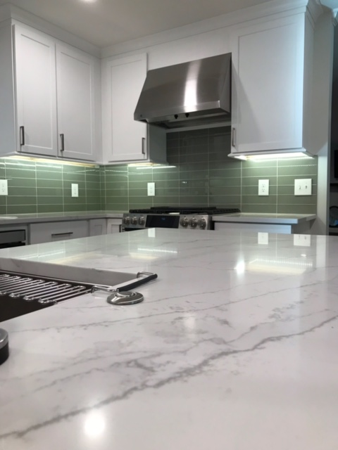 modern kitchen being installed with quartz countertops and stainless steel oven and range hood.