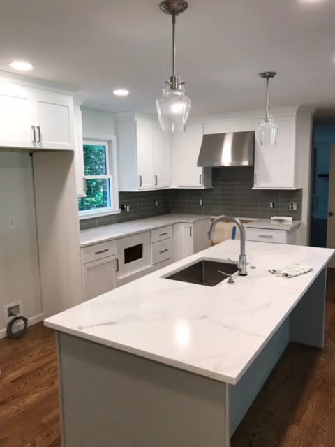 modern kitchen being renovated with stone countertops and large island with a sink