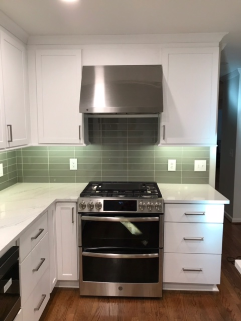 modern kitchen with stone countertops, stainless steel oven and tile backsplash