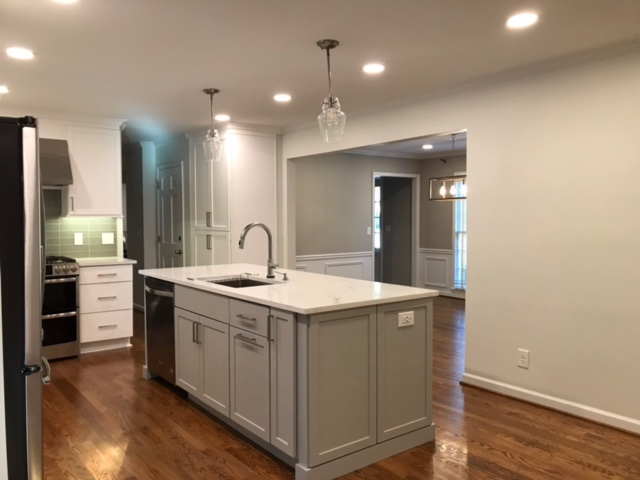 modern kitchen island with stone countertops and gray cabinets