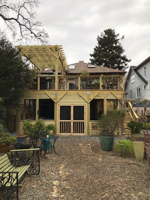 Beautiful back wood deck and pergola sitting above a screened in porch