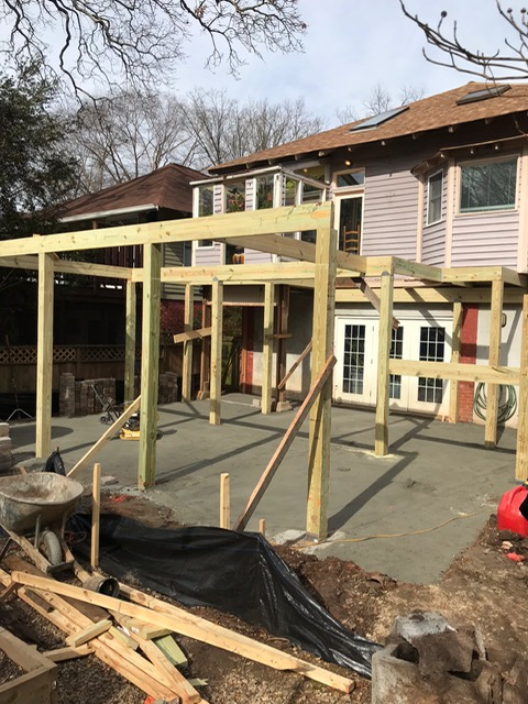 framework for wooden deck being on back of home. cement floor has been poured.