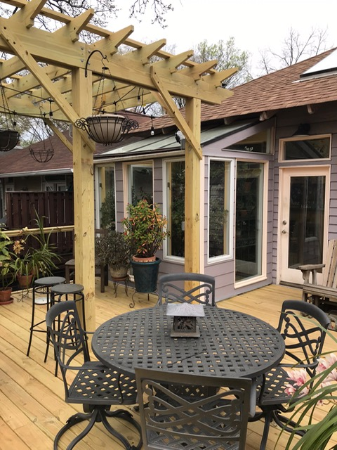 beautiful wooden back deck with pergola and patio table with chairs