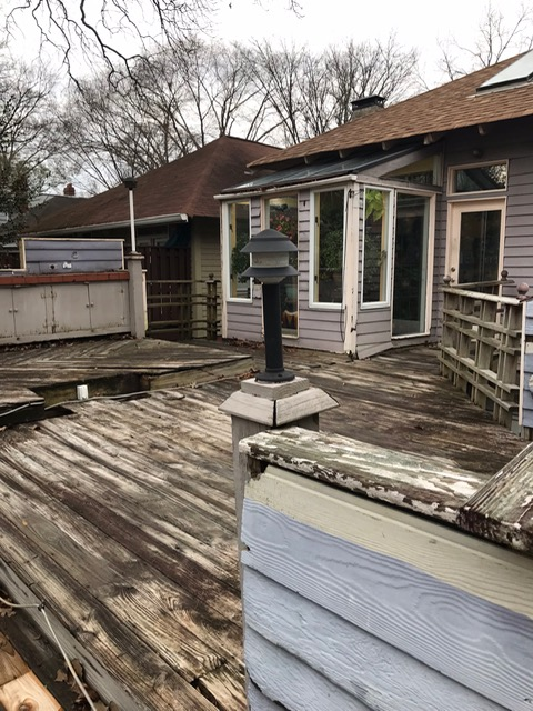 back of home with old wooden deck in disrepair