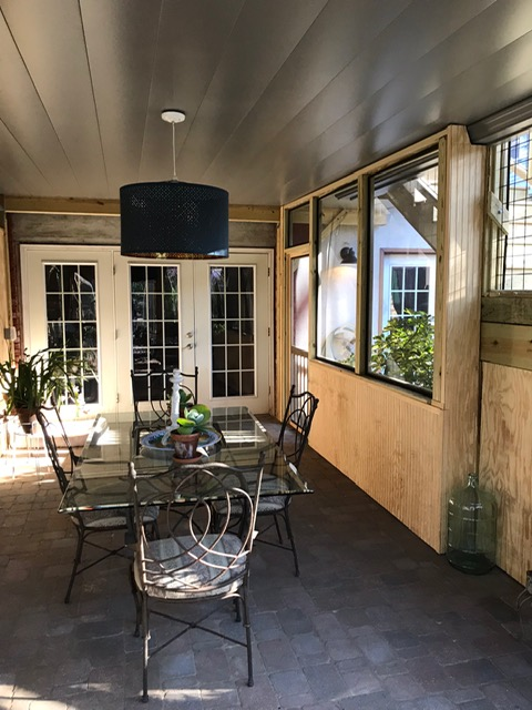 screened in porch on back of home with table and chairs