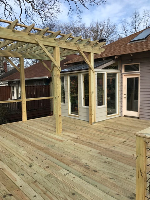 Newly constructed wooden deck with pergola on back of home