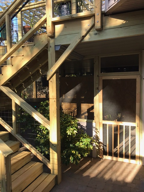 Wooden stairs on back deck and a view looking into a screened in porch