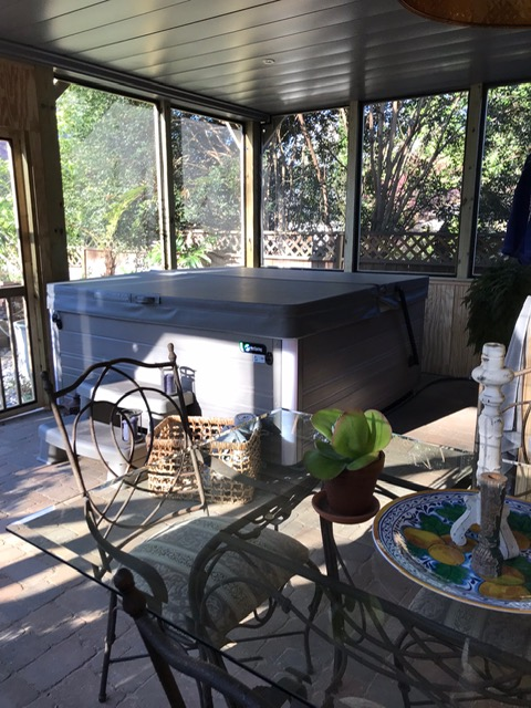 screened porch with hot tub inside