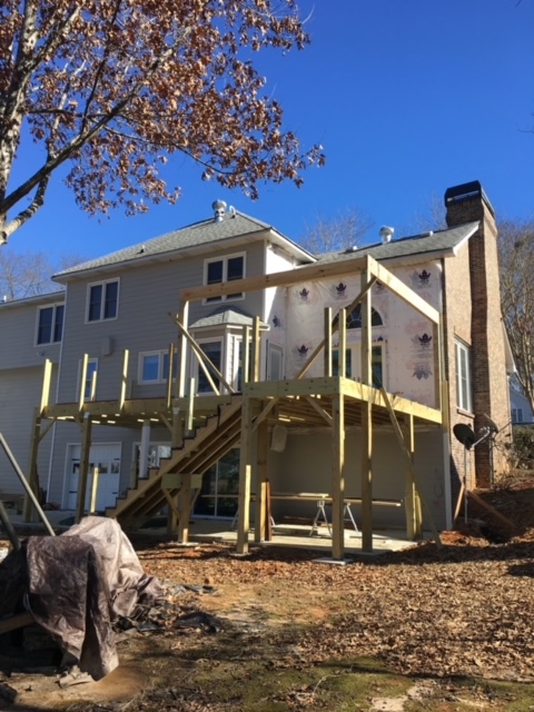 back of large home with wooden deck being constructed.