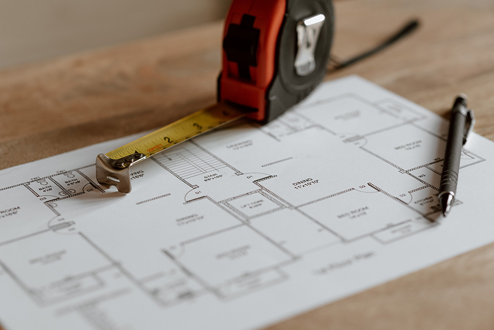 architects drawing of floor plan with tape measure and pen