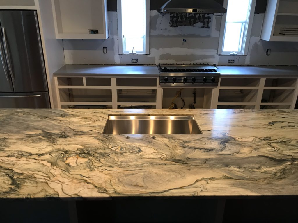 in progress construction of a modern kitchen with granite countertops and stainless steel appliances
